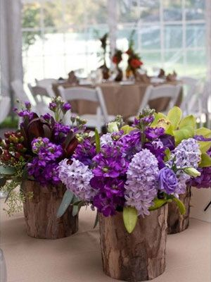 Birch pots hold hyacynth and other purple flowers at a garden style wedding setting. pretty wedding reception ideas