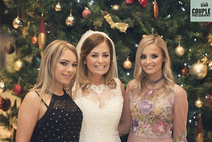 The bride & her two grown up daughters in front of the big Christmas tree. Weddings at The Westgrove Hotel by Couple Photography.