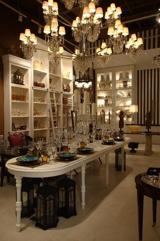 store interior with large chandelier and white long table luxury homes - Luxury Home Decor Stores
