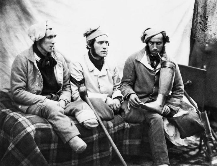 Crimean War (1854-56) casualties with amputated legs who were seen by HM Queen Victoria when she visited Chatham Hospital. Left to right - William Young, Henry Burland and John Connery. John Connery is holding his artificial leg.
