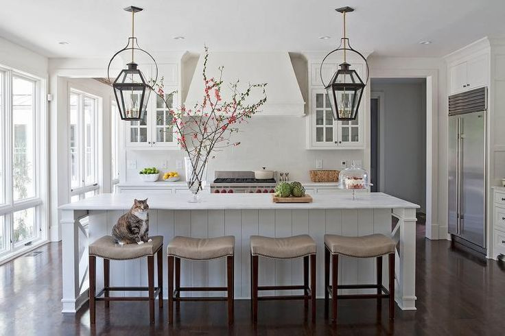 A pair of black and gold carriage lanterns hang over a white paneled kitchen island topped with white marble lined with backless taupe leather counter stools with silver nailhead trim.