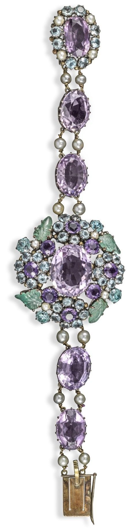 Dorrie Nossiter (attrib). An Arts and Crafts bracelet, The centre cluster is set with an oval-shaped amethyst, further clusters of amethysts, blue zircons and blue stones and foliate carved emeralds. Further oval-shaped amethysts alternately set with pair