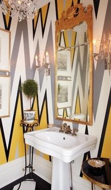 Powder Room. Zig Zag painted walls. Black. Yellow. Grey. White. Yellow. Gold. Ornate Mirror. Pedestal Sink. Crystal Chandelier.