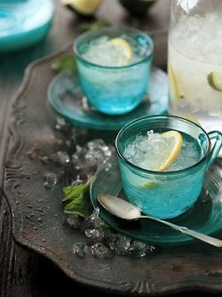 Gorgeous color - turquoise glass teacup & saucer with ice water and a lemon slice