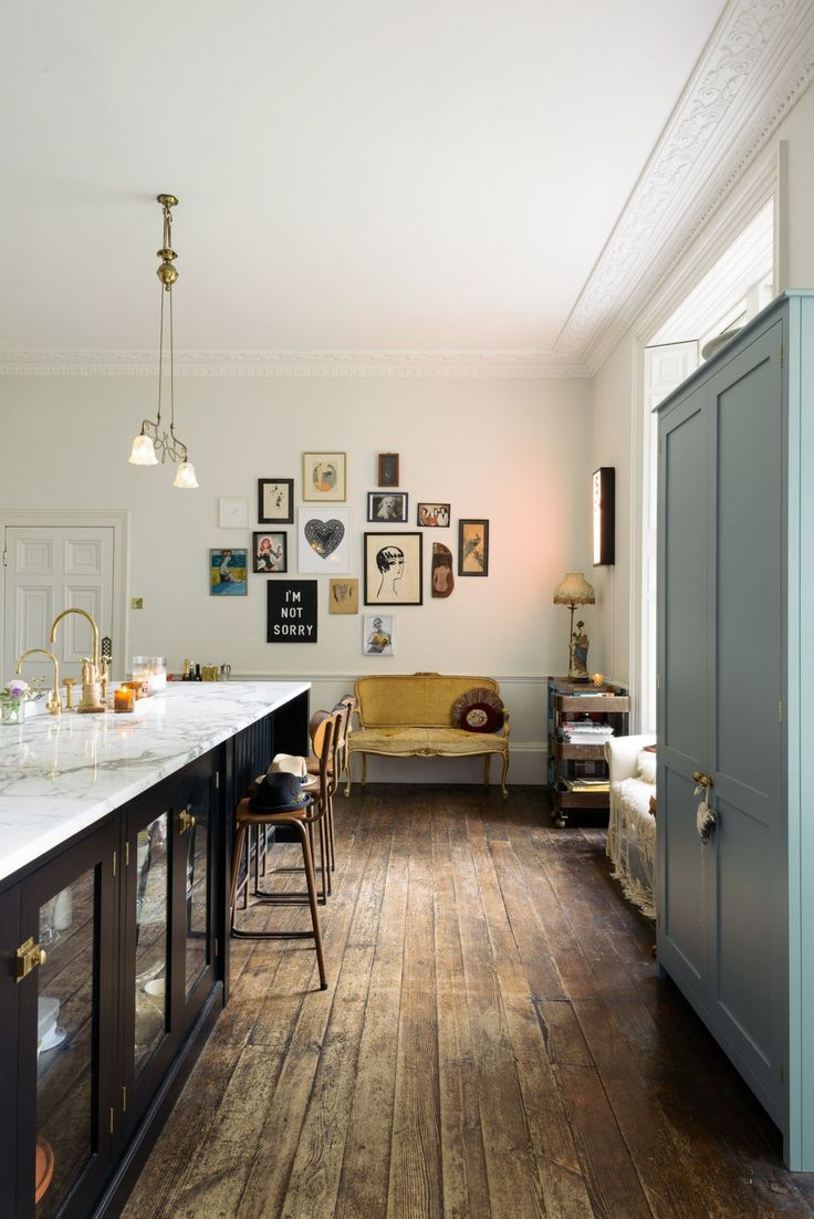 The faucet is a Brass Ionian Tap and Rinser by deVOL for Perrin & Rowe, paired with a hot water faucet. The art wall at the back of the kitchen mixes flea market finds with pieces by Zoe Grace, a contemporary artist and friend of Lowe's.