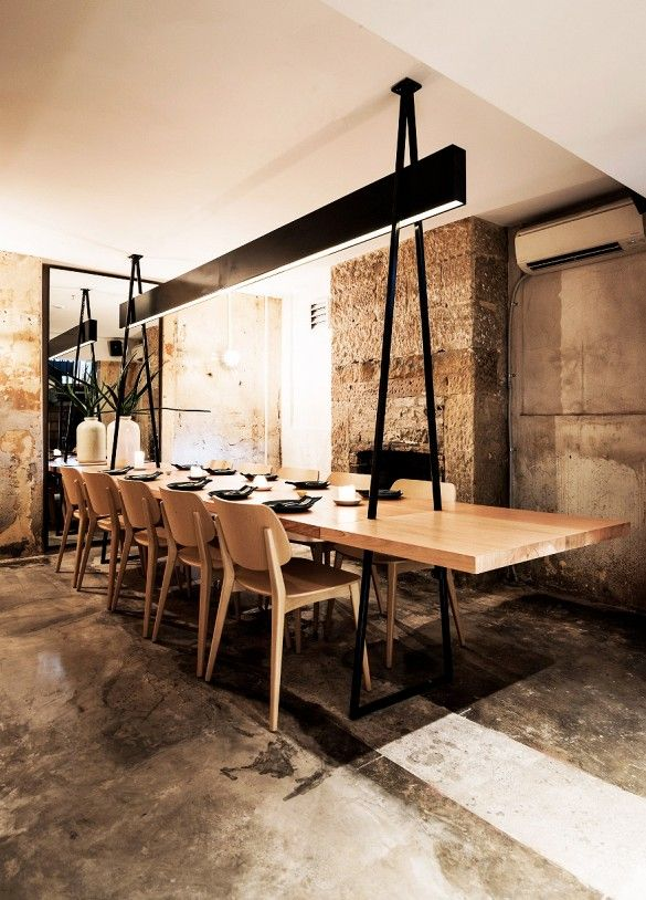 Dining space at industrial restaurant with exposed cement walls