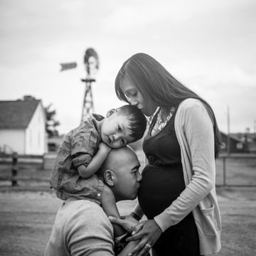 """Why it works: Oh, my goodness, this image is Love with a capital L. All those sweet kisses? That's one lucky baby in there.Pro tip: """"Finding the perfect family pose for maternity pictures will vary on the age of your other child or children,"""" photographer Amado says. """"Most of the time I work with toddlers and you have to find activities to keep them entertained on the belly. The best family pose on these occasions is the sincere joy and happiness of having big brother or sister interacting…"""