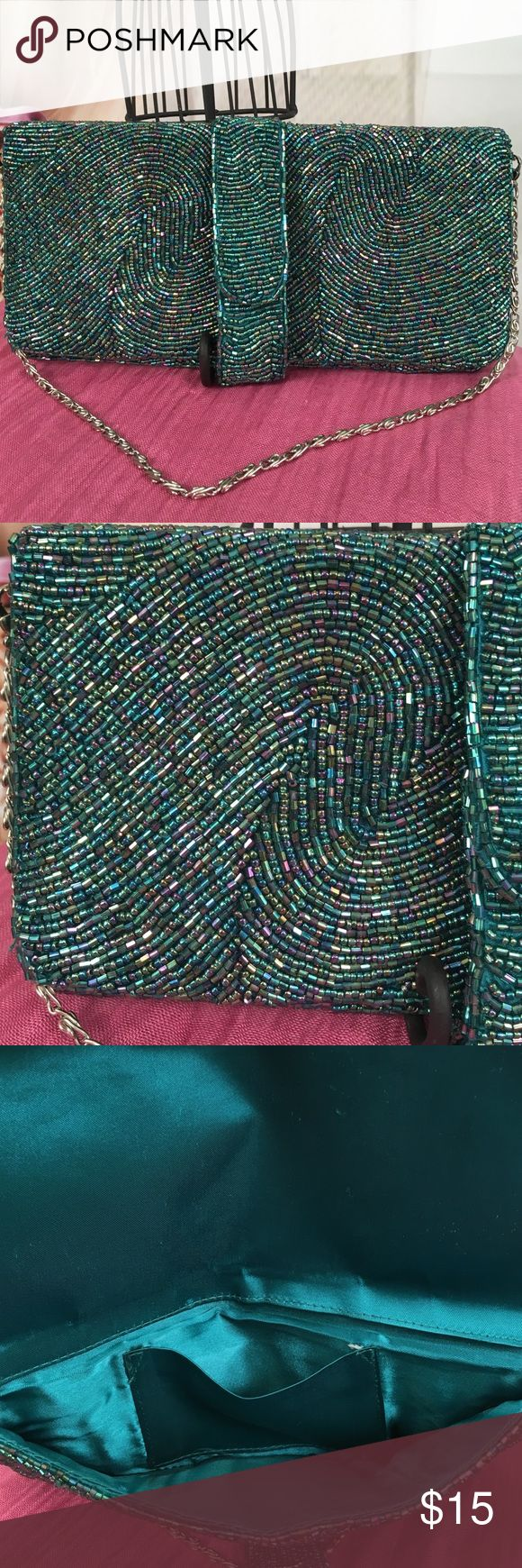 Oasis Blue Beaded Hand Clutch Today, featuring in Kaki Jo's closet is this beautiful blue beaded hand clutch.  Silver chain strap.  Beadwork is all intact.  Magnetic closure.  Good condition.  Inside the lining has a small stain, see photo.  Also there is a tiny tear where the pocket is sewn. Still gorgeous bag for evening wear! Oasis Bags Clutches & Wristlets