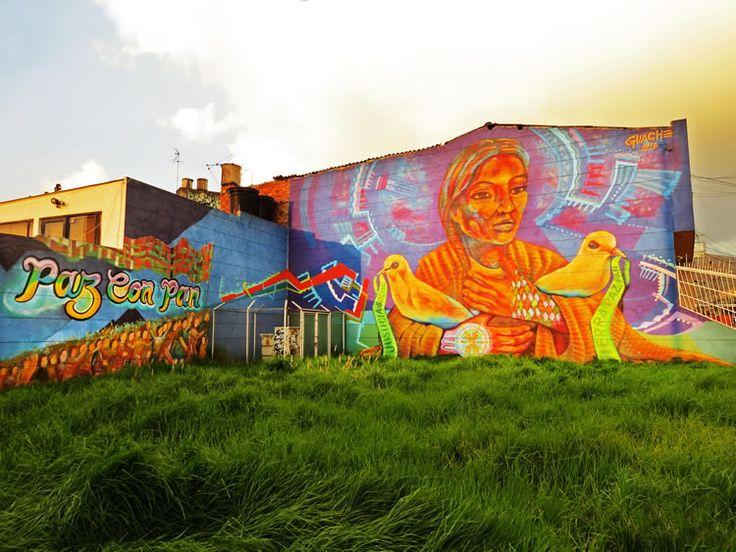 """17. Graffiti que utiliza dos fachadas en un lote de esquina de la Calle 26, con una mujer que sostiene dos palomas y el texto: """"Paz con pan""""."""