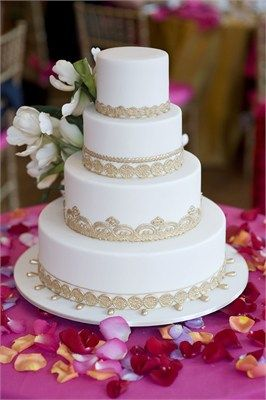 Four tier white wedding cake with intricate gold detailing