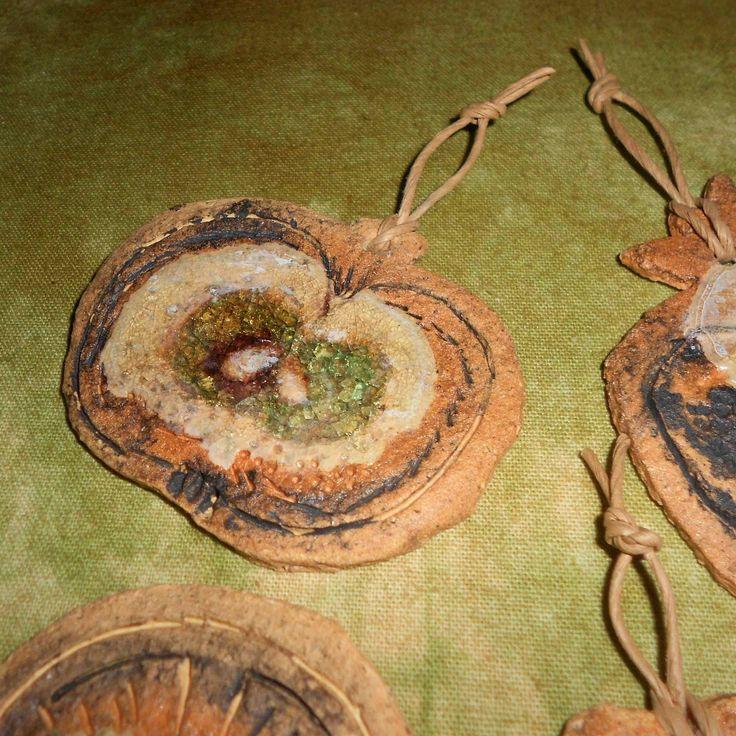 VÁNOČNÍ OZDOBY- OVOCE Popis (i pro) nevidomé: Přírodní ozdoby ze světlé šamotové hlíny, povrch je hrubší, kamínkový na omak. Snaha o tvar křížalů jablka , pomeranče, granátového jablka a ořechu. Zdobeno roztaveným sklem zelenkavo, hnědo, průhledné barvy, sklo je lehce potrhlinkované s hladkým povrchem. Okraje ozdob jsou patinovány hnědou barvou, zdobeny vyrytými ...