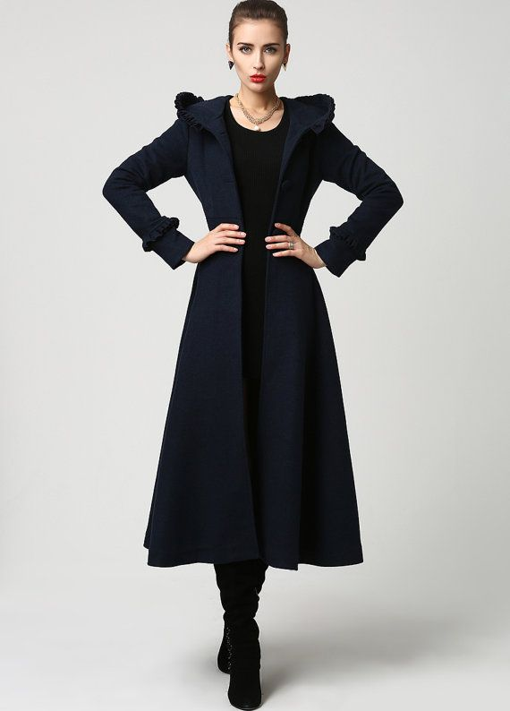 This stunning long woman's coat is beautifully fitted and tailored for a classic, feminine design. It features a slim fitting bodice with elongated sleeves and tapered waist band leading into a long, flowing skirt. The hood, shoulders and sleeve cuffs have a pretty ruffle detailing that