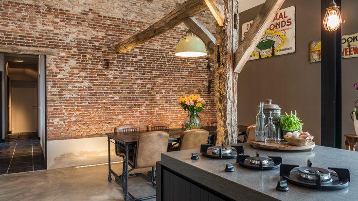 Ontmoeting van de woonbetonvloer met de oude gemetselde muur, de oude houten spanten en de woonkeuken.