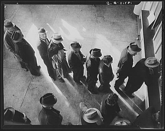 Line of men inside a division office of the State Employment Service office at San Francisco, California, waiting to register for benefits on one of the first days the office was open. They will receive from six to fifteen dollars per week for up to sixteen weeks. Coincidental with the announcement that the federal unemployment census showed close to ten million persons out of work, twenty-two states begin paying unemployment compensation. -- Dorothea Lange. Library of Congress #