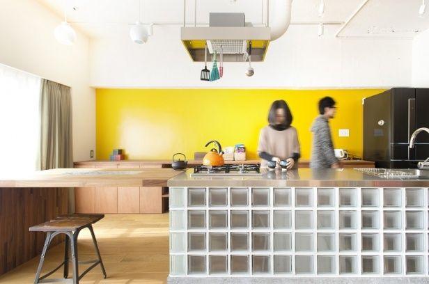 ワイドなオープンキッチンはダイニングテーブルとひと続き。「どこかにガラスブロックを使いたい」という夫の要望は、キッチンで実現した。からし色の壁は妻のセレクト。