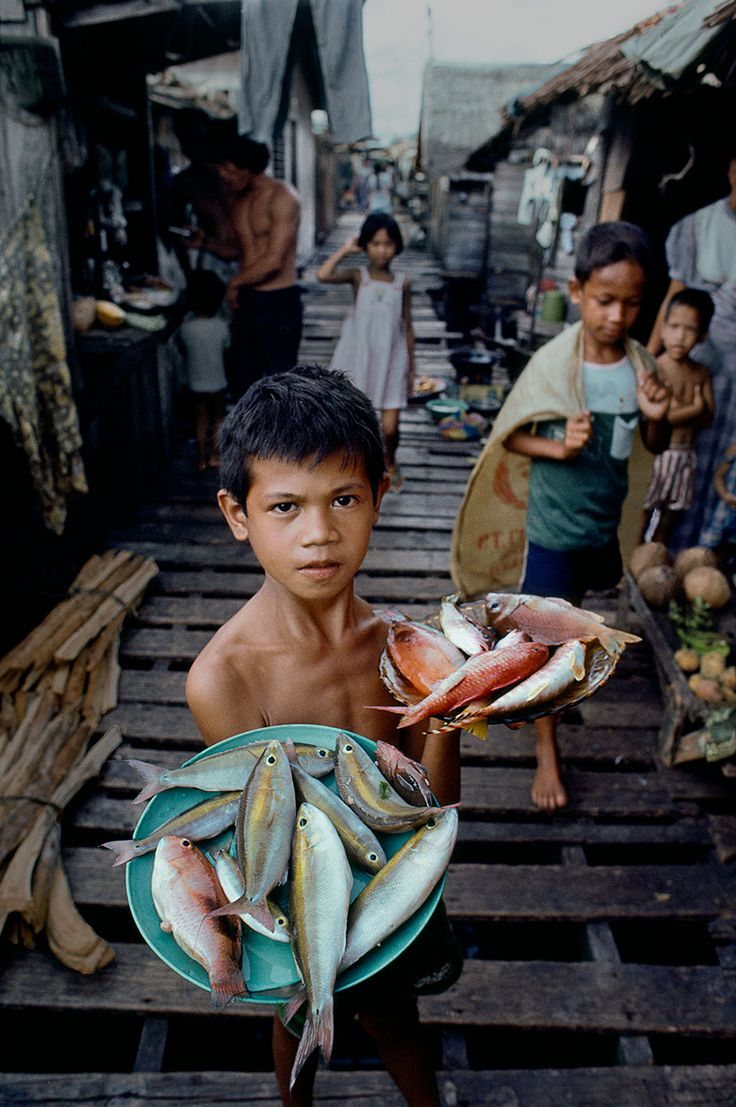 Philippines - Steve McCurry. The perspective leads our eye straight to the young boy. This image is like a teaser because now the viewer wants to know more about life there and the story of the boy.