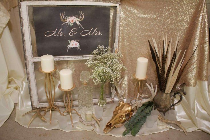 Head table decor.  Sequins tablecloth. Old window. Tapered candles. Vintage pitcher. Deer skull and antlers.  Eucalyptus. Baby's breath. Mismatched glass bottles.  Rustic woodland Glam Boho Wedding reception