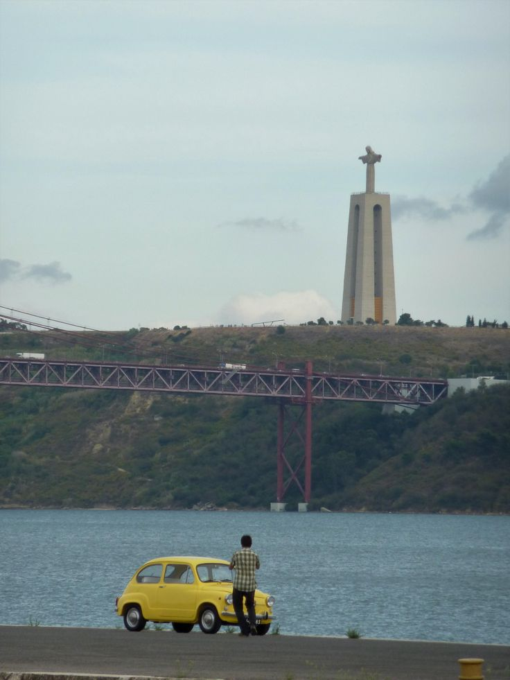 Man with his yellow Fiat 600 looking towards the 25 de Abril Bridge and the Sanctuary of Christ the King Lisbon Portugal. [OC] [2736 x 3648]