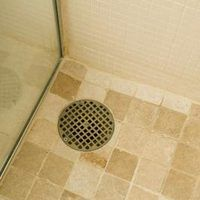 When a new shower is installed, a fiberglass shower pan is often used. A fiberglass pan provides a strong, stable base for the person using the shower to stand on, but it's also plain-looking and can detract from the appearance of the shower. You can improve the appearance of the shower by laying tile over the fiberglass pan.