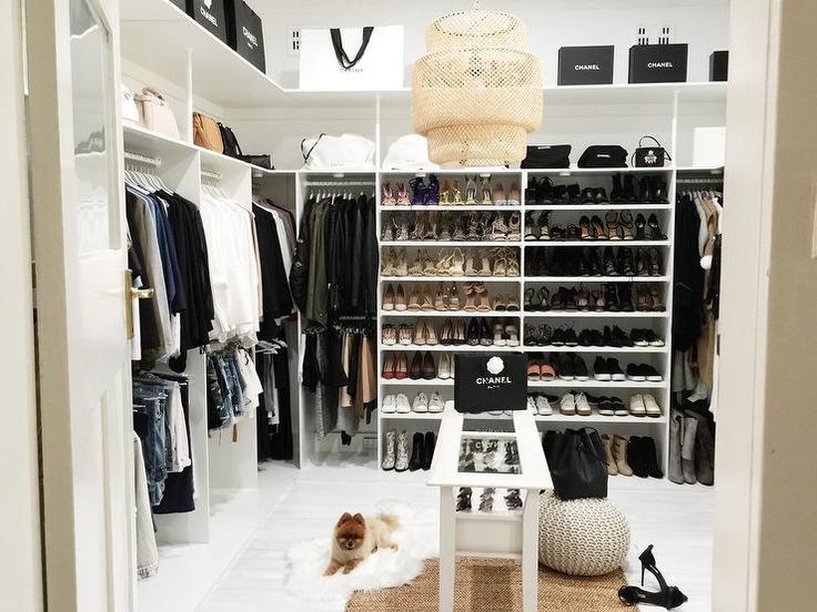 Extra bedroom turned walk in closet features a white modular closet system boasting clothes rails, shoe shelves and bag shelves lined with Chanel bags and boxes.