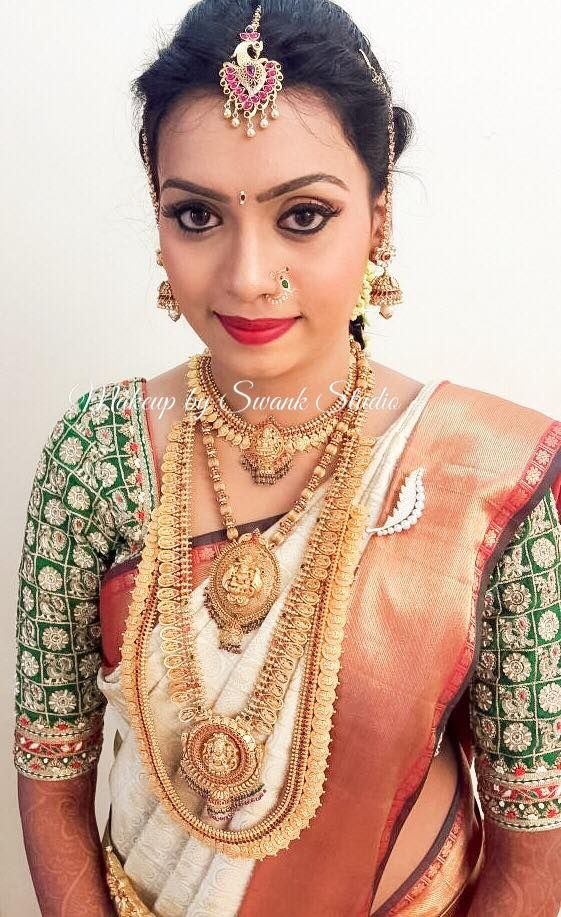 Traditional Southern Indian bride, Vidya wears bridal silk saree and jewellery for her Muhuratam. Makeup and hairstyle by Swank Studio. Red lips. Nose ring. Eyebrows. South Indian bride. Eye makeup. Bridal jewelry. Bridal hair. Silk sari. Bridal Saree Blouse Design. Indian Bridal Makeup. Indian Bride. Gold Jewellery. Statement Blouse. Tamil bride. Telugu bride. Kannada bride. Hindu bride. Malayalee bride. Find us at https://www.facebook.com/SwankStudioBangalore