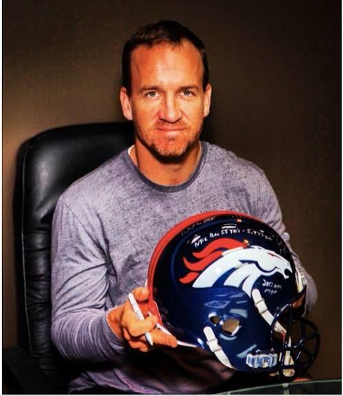 Peyton Manning signing a Broncos Helmet. Nice, nice facial hair.