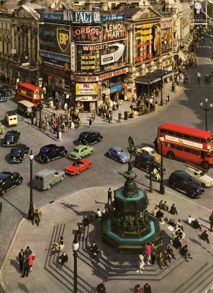 Picadilly Circus , London. Just look at the old cars and brand logos on the sides of the buildings!