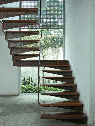 """Ao somar um pavimento a esta casa, o arquiteto Marcelo Ferraz, do escritório paulista Brasil Arquitetura, precisou criar uma escada. """"Queria algo que causasse surpresa"""", conta. A peça de dois lances idênticos emprega chapas de aço corten maciço e pisadas de ipê (123 x 32 cm) tratadas com resina. O patamar inferior é fixo por meio de uma placa de aço na parede e o superior, por mão-francesa presa à viga que sustenta o mezanino. Um tubo contínuo de aço corten funciona como corrimão. Execução…"""