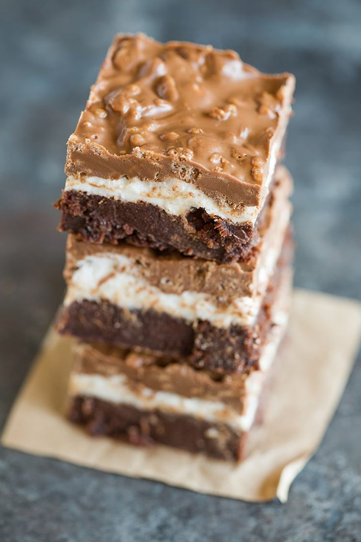 Marshmallow Crunch Brownie Bars - A stack of brownies with a layer of marshmallows and crisp chocolate and peanut butter topping.