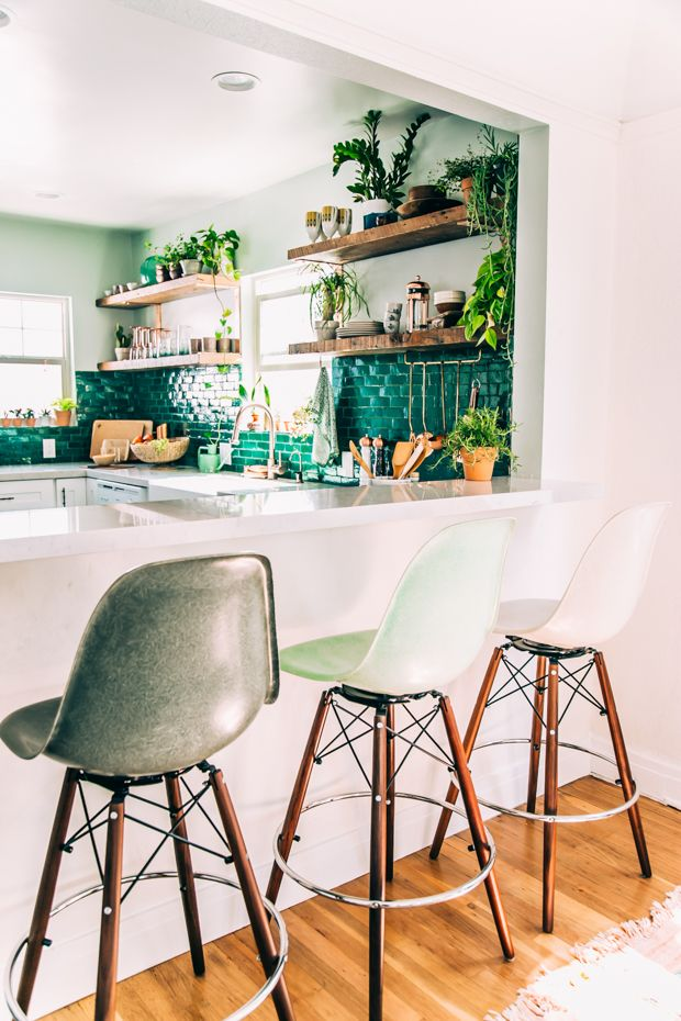 壁に深いエメラルドグリーンのタイルの貼られたキッチンをダイニングカウンターから