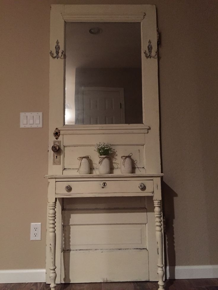 """Vintage farmhouse hall tree. Old door, farmhouse table cut in half with a touch of """"old white"""" chalk paint to blend the two together. Mirror spray paint used to make the glass in the door look like an old antique mirror. So happy with the results!"""