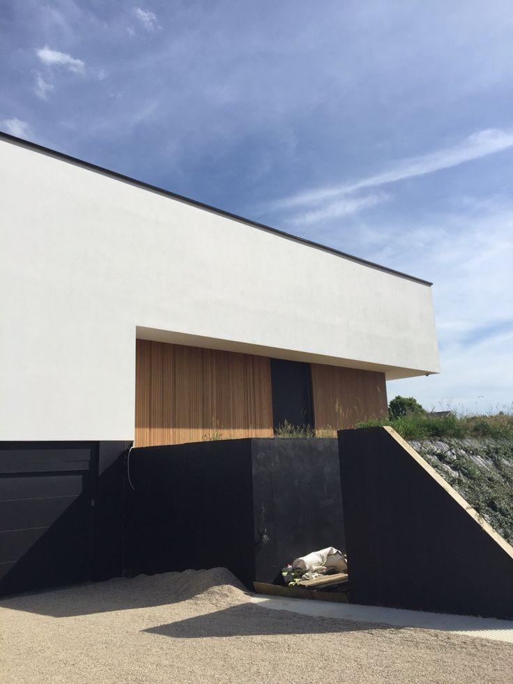 Moderne woning :: gevel met witte crepie, zwarte aluminium dakrand, ramen, deur en hout accent