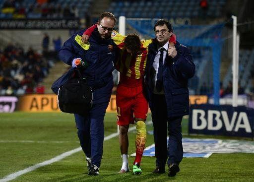 El delantero brasileño Neymar sale del campo lesionado ayudado por miembros del cuerpo médico del FC Barcelona, durante el partido ante el Getafe, por octavos de final de la Copa del Rey española, en el estadio Coliseo Alfonso Pérez, en Getafe, el 16 de enero de 2014. | Ver foto - Yahoo Deportes