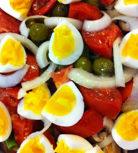 Spinach salad with tomatoes, eggs, olives & onions