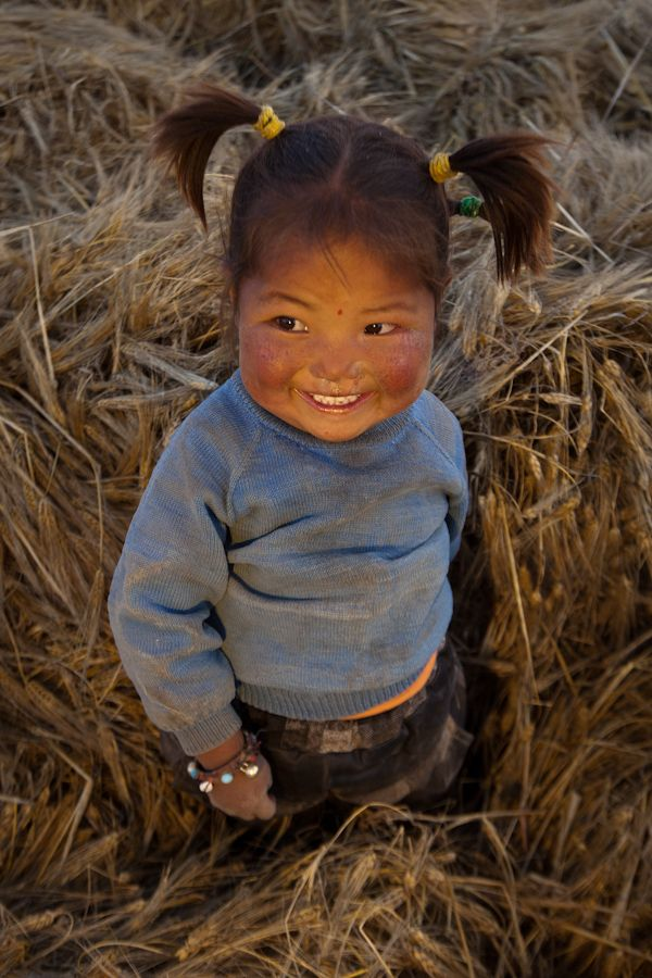 Tibetan girl playing at dusk amongst freshly cut wheat; Patrick, picto.asia