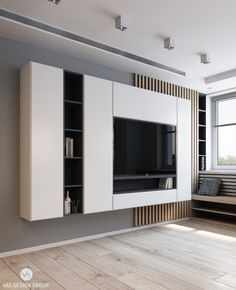 From behind the couch, a monochromatic panel housing TV and entertainment essentials meets the eye. Light wooden flooring, muted grey walls and a lack of clutter help it dominate the space.