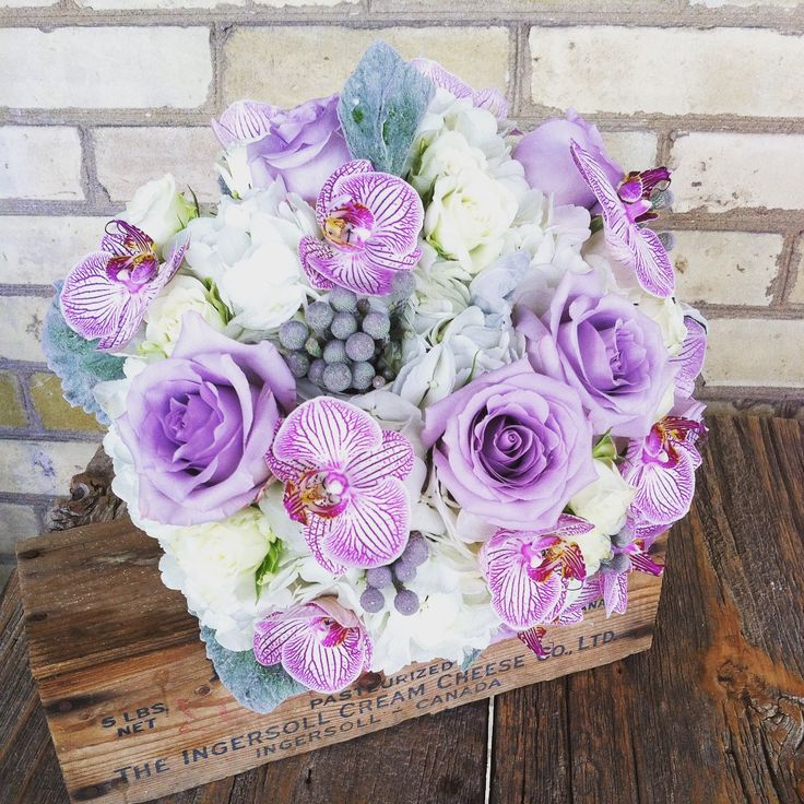 Jeanelle's bouquet of fresh roses, orchids, and gray accents for an August Wedding. Designed by Olive Lane