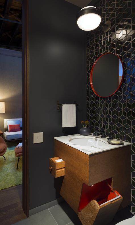 IL BAGNO IN CAMERA Rivestito con le piastrelle a disegno grafico di Heath. Il lampadario vintage firmato Sergio Mazza. Il vano a ribalta nel mobile del bagno serve a contenere le riviste. Nella stanza da letto si intravede la 'Womb Chair' vintage di Eero Saarinen.