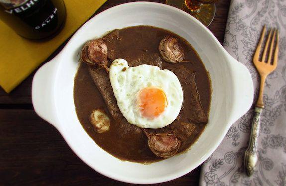 Um bife delicioso temperado com sal, alhos, pimenta e louro, cozinhado num molho feito à base de café, leite e vinho tinto, servido com ovos estrelados.