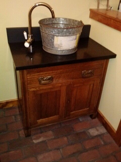 Repurposed bucket and washstand used as a bathroom sink and vanity in the laundry room the top Used bathroom vanity with sink