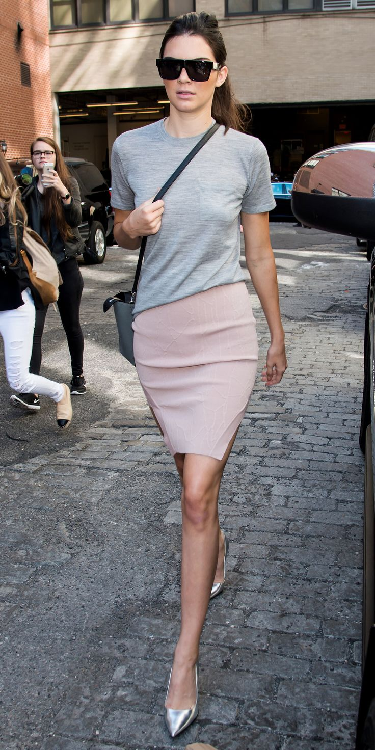 Kendall Jenner took a break from the New York Fashion Week runways to attend brother-in-law Kanye West's Yeezy presentation, where she opted for casual-cool elegance in a heather grey tee tucked into a pale link Jonathan Simkhai skirt. She topped off the ensemble with Saint Laurent sunnies, a Michael Kors bag, and Tom Ford pumps. - September 16, 2015 - from InStyle.com
