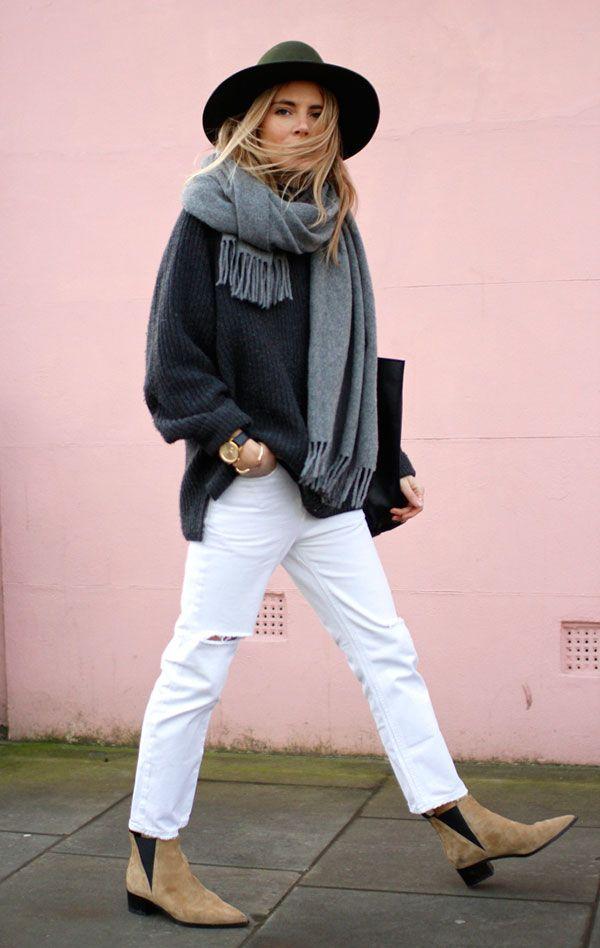 Street style look com suéter cinza, calça branca, bota bege e chapéu verde.
