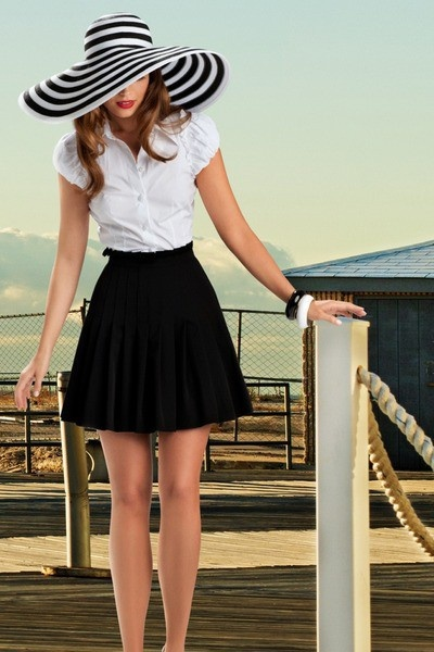 We love the retro, summery vibe of the striped floppy hat paired with a simple white blouse and black pleated skirt.
