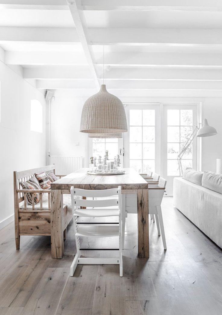 salle à manger scandinave blanche aménagée avec une table à manger et un banc en bois massif et un parquet en bois massif clair