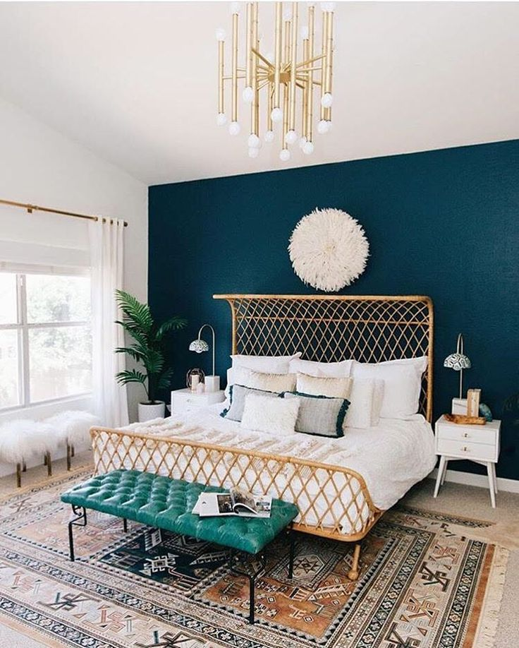 Stunning modern bohemian bedroom with brass chandelier, tufted leather bench, woven rattan sleigh bed frame and dramatic teal accent wall.