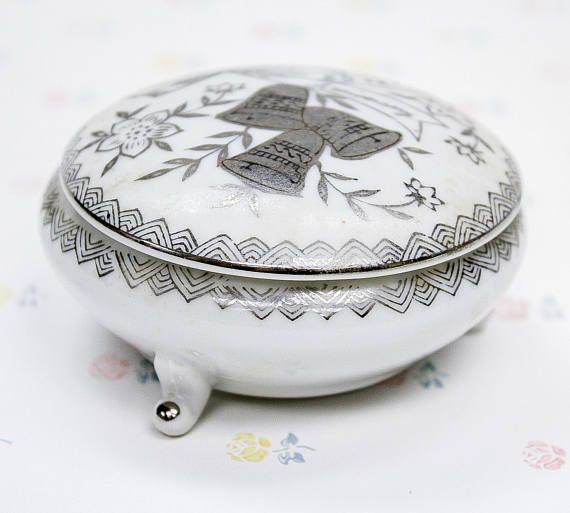 A white porcelain jewelry/trinket box for the happily married couple celebrating their 25th anniversary! Beautiful silver detailing on the lid and along the top edge of the container base is in great condition still. Written on the bottom is B-225 Japan  Dimensions: 6.5 x 5 x 2cm