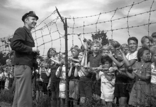 "Gail Halvorsen ""the candy bomber"" greeting children in the then isolated West Berlin 1948-49 after dropping candy from the air in tiny parachutes"