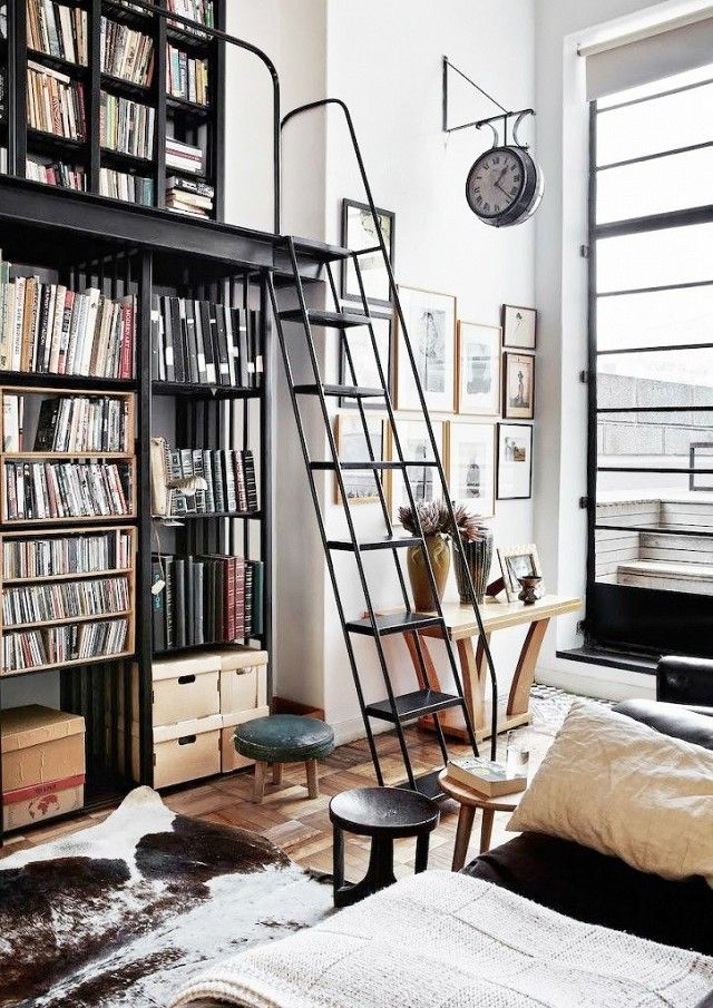 An enviable home library with a ladder and a mounted vintage clock