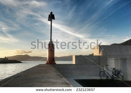 lighthouse over dam with seascape in the background - stock photo