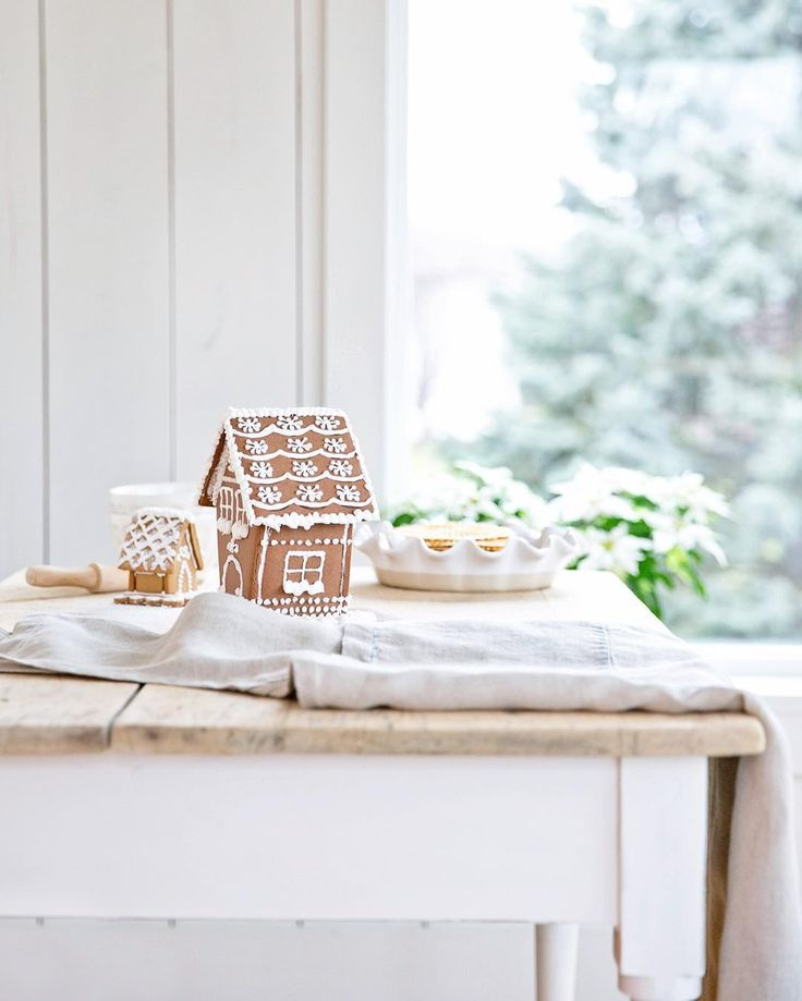 Serene white French country Christmas kitchen with gingerbread houses upon a rustic farm table - A Rosy Note. #gingerbreadhouses #christmaskitchen #whitechristmas #christmasbaking #farmhousechristmas